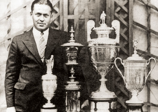 Bobby Jones standing next to a collection of trophies