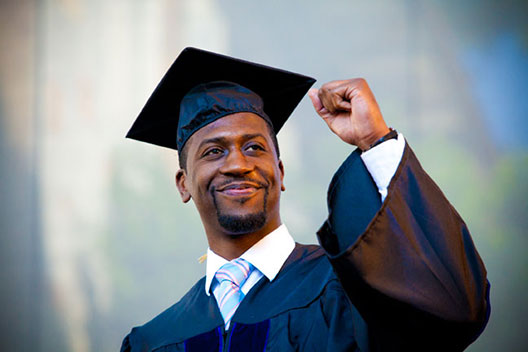 A male student in commencement regalia smiles and holds his fist in a victory gesture
