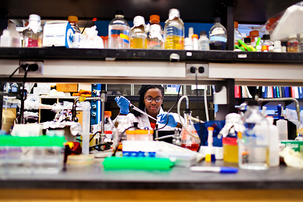 African-American student works diligently in a laboratory setting.