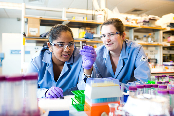 Two female students with blue lab coats and goggles work diligently in the lab.