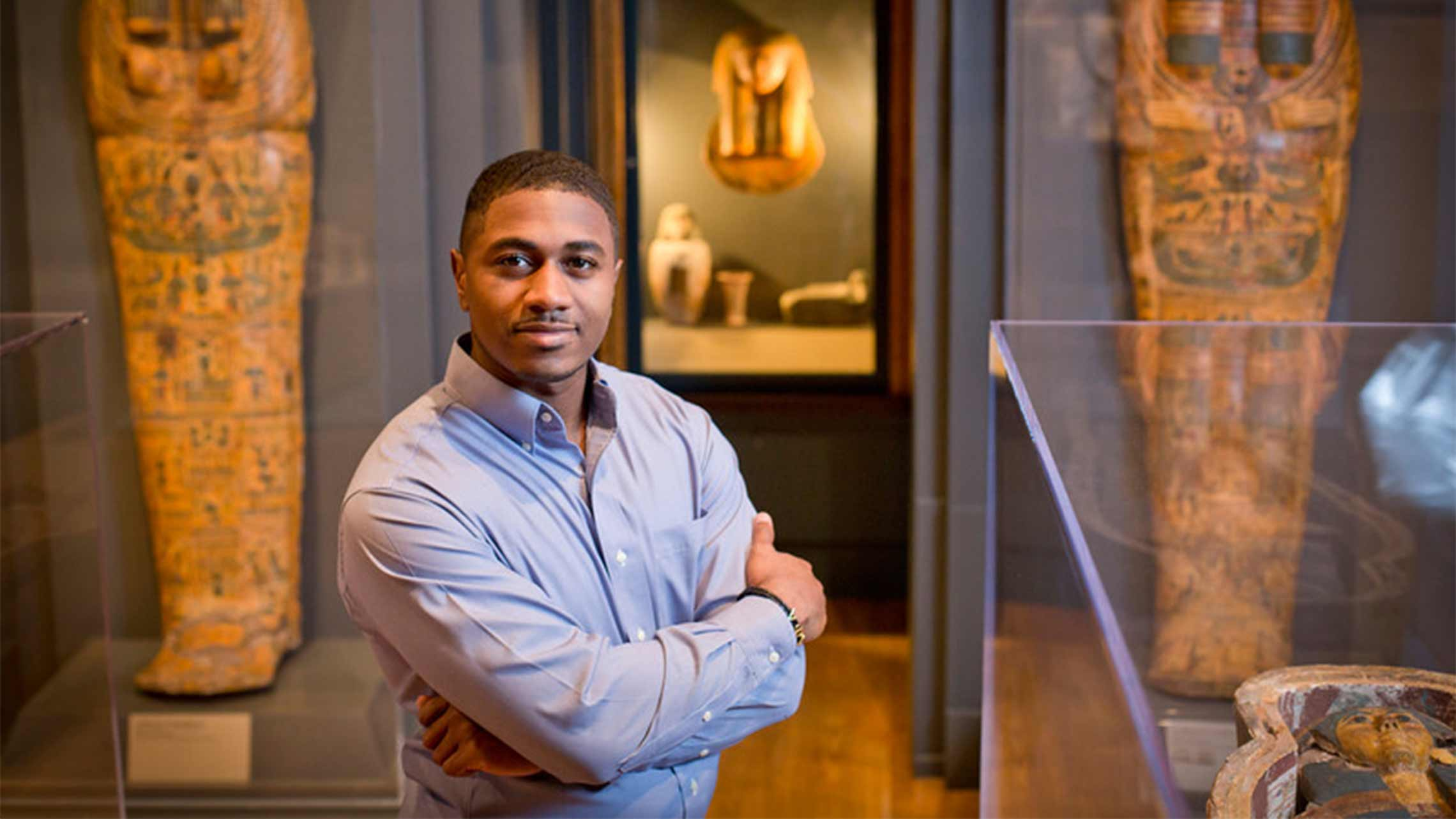 African American male poses in the Art Museum between two exhibits.