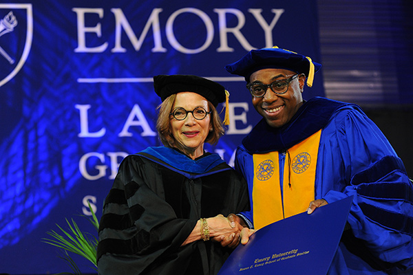 Laney Graduate School hooding ceremony photo of a male graduate posing with the Dean after being hooded.