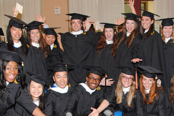 The photo includes 14 male and female graduates in black commencement regalia celebrating happily.